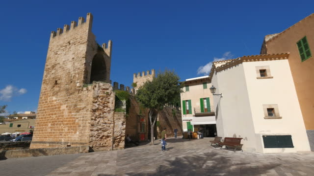 medieval town wall and gate of alcudia, majorca, balearic islands, spain - gemeinsam gehen stock-videos und b-roll-filmmaterial