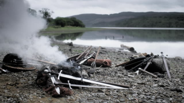medieval weapons and campfire beside lake - war and conflict stock videos & royalty-free footage