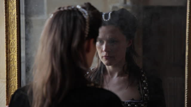 medieval woman looking at herself in a mirror - medieval era reenactment . - rievocazione video stock e b–roll
