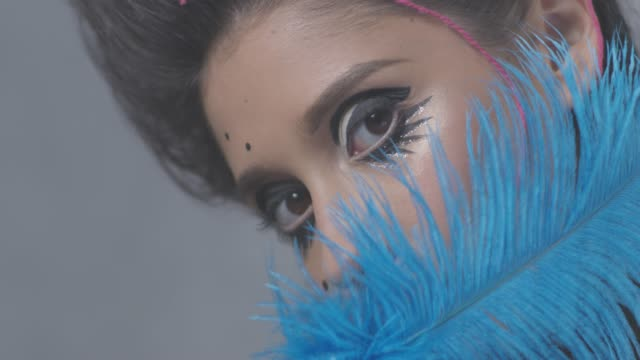 Medieval-like brunette fashion model plays with blue ostrich feather. Fashion video.