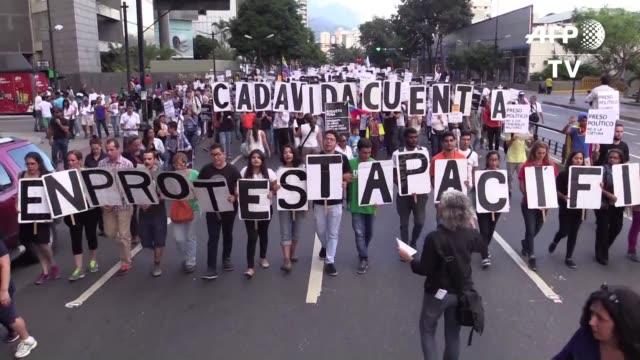 vídeos de stock e filmes b-roll de medio millar de opositores venezolanos marcharon el miercoles en caracas para recordar a los fallecidos en las protestas contra el mandatario nicolas... - exigir