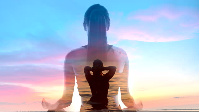 ws meditating against a background of a woman swimming in the sea and cloudscape at sunset - lotus position stock videos & royalty-free footage