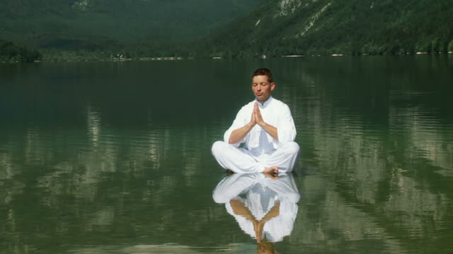 hd crane: meditating in a lake - buddhism stock videos & royalty-free footage