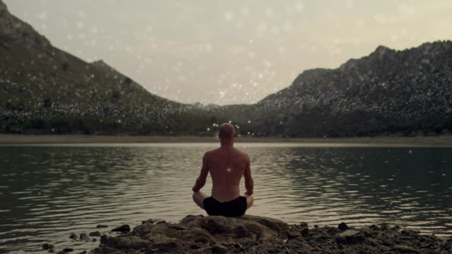 meditating man healing cosmic energy - lotus position stock videos & royalty-free footage