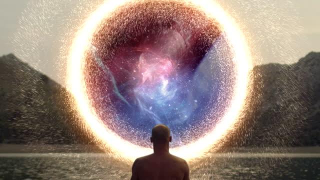 meditating man opening gate to cosmic energy - consapevolezza video stock e b–roll