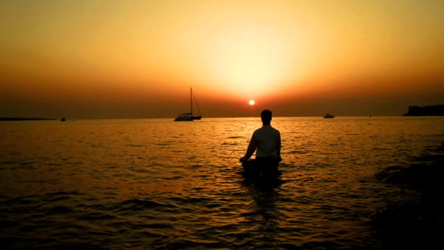 HD: Meditating On Rock In The Sea At Sunset