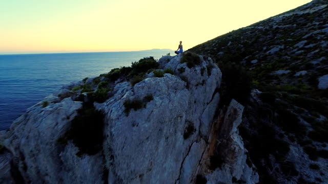 aerial meditating on the cliff at dusk - cliff stock videos & royalty-free footage