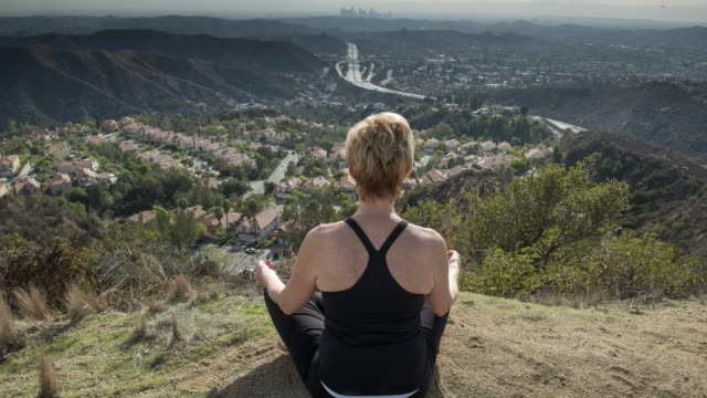 meditating with view of downtown la -  time lapse - glendale california stock videos & royalty-free footage