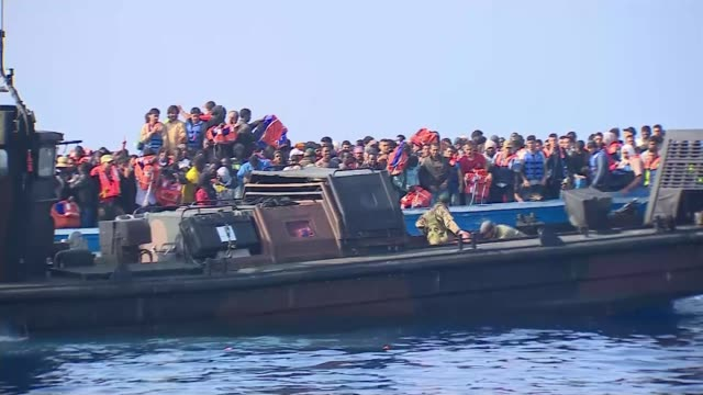 mediterranean migrant crisis: hms bulwark rescue mission; mediterranean sea: ext soliders in boat from hms bulwark alongside migrant boat back view... - emigration and immigration stock videos & royalty-free footage