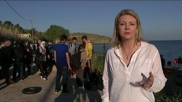 migrants landing on holiday island of lesbos reporter to camera various of migrants along with bags - 2015 stock-videos und b-roll-filmmaterial