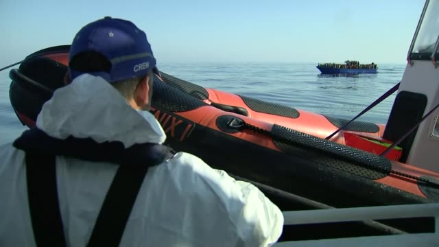 number of migrants reach record high / migrants increasingly reliant on private rescuers at sea off libyan coast ext prow of boat along through sea... - passagier wasserfahrzeug stock-videos und b-roll-filmmaterial