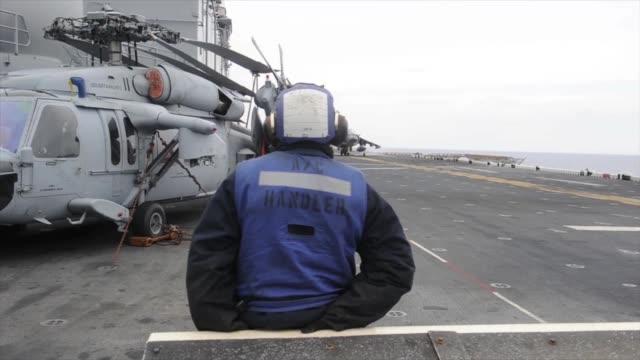 vídeos de stock e filmes b-roll de mediterranean sea - sailors and marines guide an av-8b harrier ii for takeoff aboard the multipurpose amphibious assault ship uss bataan . the bataan... - número 6