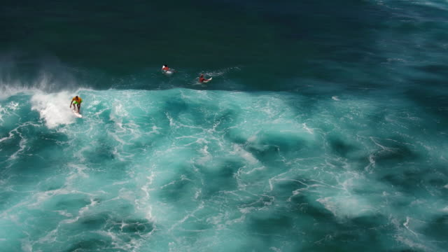 medium aerial shot of three surfers trying to catch a wave and one actually surfing it - kahuku stock videos & royalty-free footage