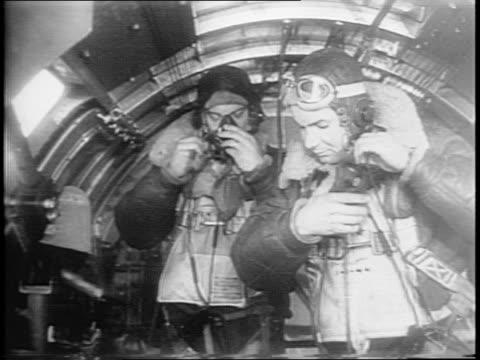 medium and close up shots of bomber and soldiers loading bombs inside a hangar / close up shot of bomb bay doors closing beneath bomber in hangar /... - 多国籍軍点の映像素材/bロール