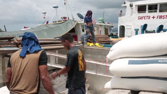 medium and wide shots, workers offload flour from a boat docked in the port at puerto princesa, palawan, the philippines - moored stock videos & royalty-free footage