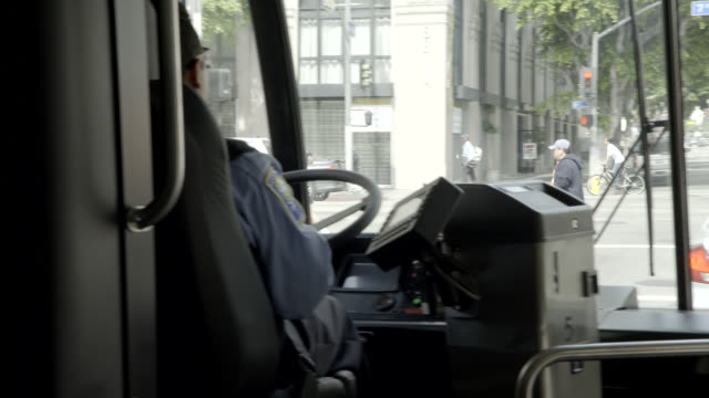 medium angle moving pov from bus driving through city streets. broadway. driver visible.