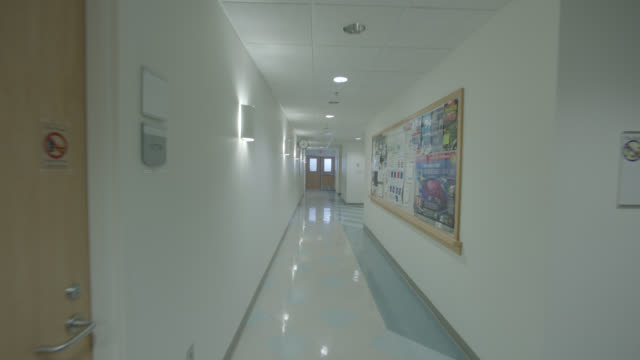 medium angle moving pov of hallway in hospital. - korridor bildbanksvideor och videomaterial från bakom kulisserna