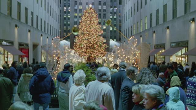 medium angle of a crowd around the christmas tree in rockefeller center. - rockefeller center christmas tree stock videos & royalty-free footage