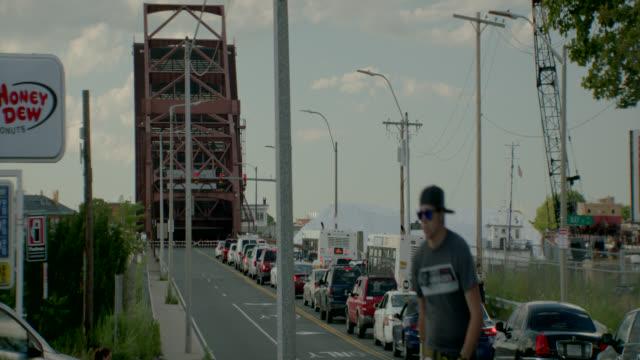 medium angle of andrew mcardle bridge, meridian st. drawbridge. cars and buses waiting in traffic on city street,. - drawbridge stock videos and b-roll footage