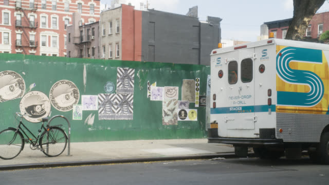medium angle of artwork on wall. posters visible. bicycle parked on rack. pedestrians. phone service truck visible. apartment buildings in bg.