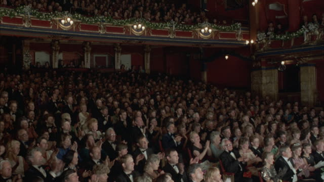 medium angle of audience clapping and giving applause. pans right to left at start, audience is dressed in formal evening wear. woman starts to walk from aisle at left at end. - formal stock videos & royalty-free footage