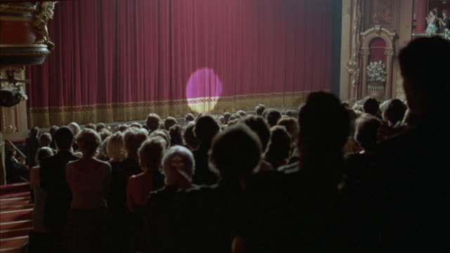 Medium angle of audience wearing evening formal wear at theater standing and giving applause, standing ovation, towards stage. curtain drops on stage, then spotlight illuminates circle on curtain. curtain begins to move back at end.