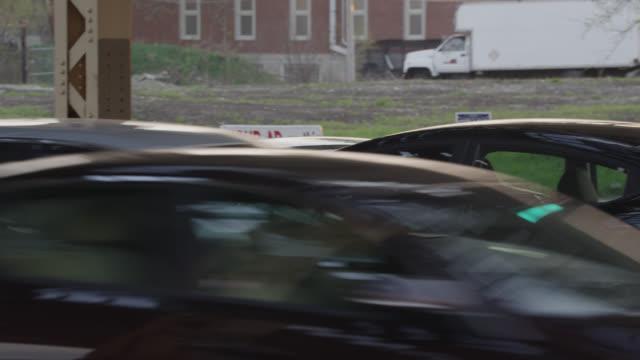 medium angle of cars on city street in near collision. - winkel stock-videos und b-roll-filmmaterial