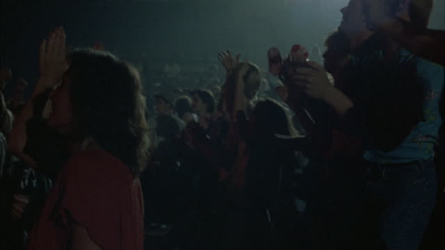 medium angle of cheering crowd at concert. pov from side of crowd. pan r-l of rows of fans. - bleachers stock videos and b-roll footage