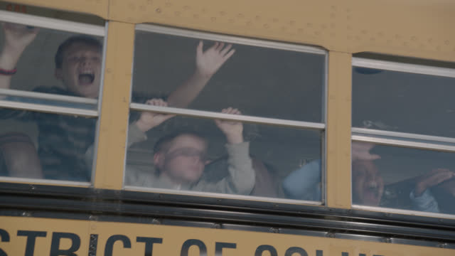 medium angle of children on school bus looking out windows. bus shakes and kids scream. could be attack, invasion, emergency, or natural disaster. - risk stock videos & royalty-free footage