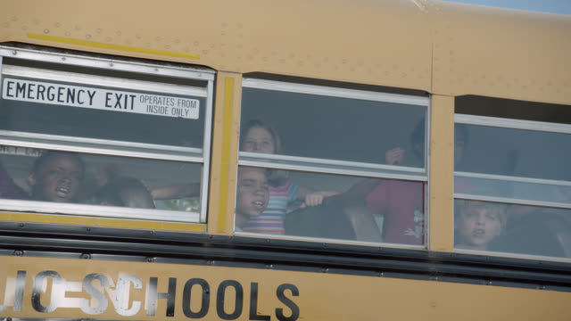 medium angle of children on school bus looking out windows. bus shakes and kids scream. could be attack, invasion, emergency, or natural disaster. - bus stock videos & royalty-free footage