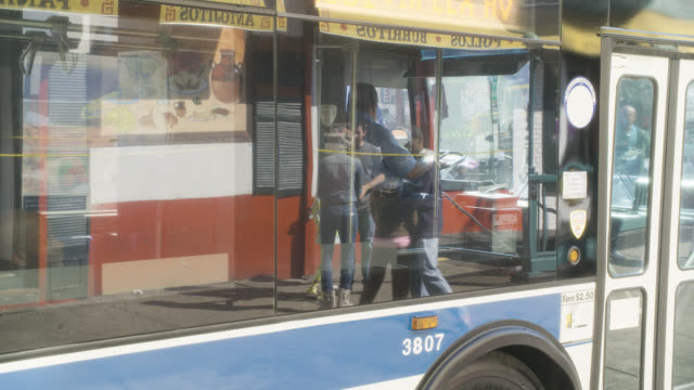 medium angle of city bus. reflection of storefront and restaurants visible on side of bus.