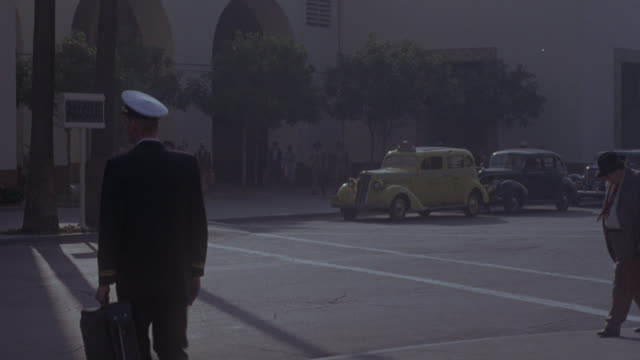 vidéos et rushes de medium angle of city street and sidewalk in front of union station. see pedestrians and soldiers in formal military dress walk by in foreground. see 1940's era classic cars drive by. - union station los angeles