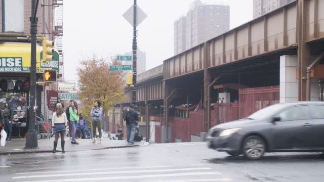medium angle of city street near elevated train bridge. pedestrians visible. cars driving.