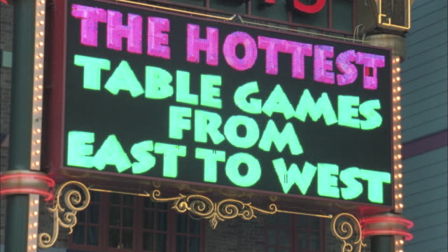 medium angle of coloful electronic billboard that changes text.  hung underneath large bally's casino sign. - western script stock videos & royalty-free footage