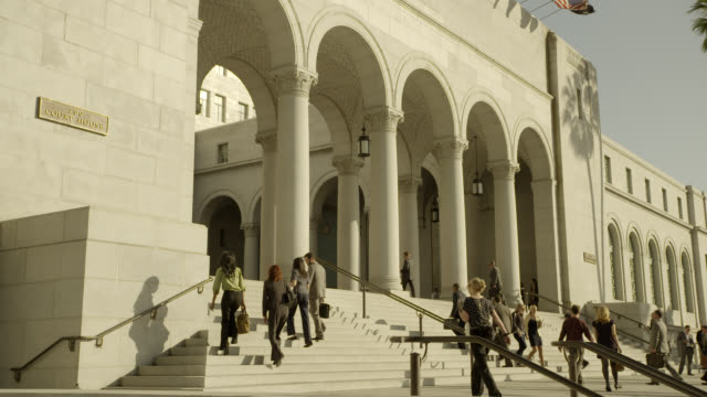medium angle of courthouse entrance arches and stairs. people or pedestrians. government building. actually los angeles city hall. - palazzo di giustizia video stock e b–roll