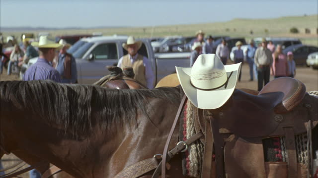 medium angle of cowboy hat sitting atop saddle on horse. horses tied to hitching post. people with cowboy hats walk around in parking lot. could be rodeo.