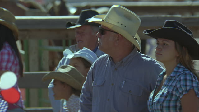 medium angle of crowd of people in cowboy hats standing in arena. could be rodeo. - ロデオ点の映像素材/bロール