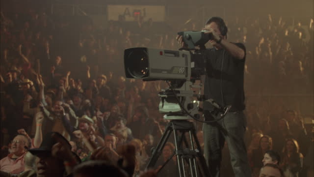 medium angle of crowd of spectators at country music concert. people wear western shirts and cowboy hats. camera pans up to cameraman or crew preparing stage lights and cameras. people clap.