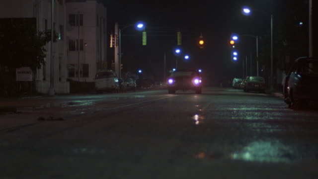 medium angle of dark empty urban city street. see fluorescent street lights and puddles throughout. see sedan with headlights on poised toward pov at end of street. see male in green shirt run left to right across street. see string pulled and car move fo