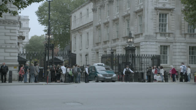 medium angle of double decker bus on city street near entrance to 10 downing street and government buildings. whitehall sw1. pedestrians, tourists, and cars visible. suv pulls out of gate. - downing street stock videos & royalty-free footage