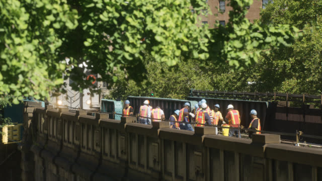 medium angle of elevated train on bridge. workers in hardhats visible. - elevated train stock videos & royalty-free footage