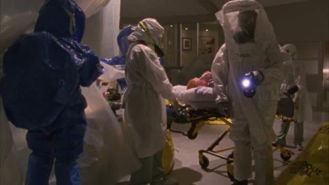 medium angle of emergency room team or crew dresses in hazmat biohazard suits. men and women with gas masks covered from head to toe in white and scrub blue suits. man being pushed on stretcher, gurney, or hospital bed. large yellow hazardous material was - radiation stock videos & royalty-free footage