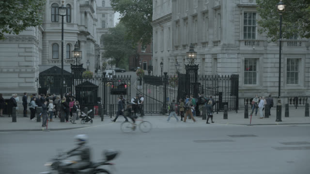 medium angle of entrance to 10 downing street and government buildings. whitehall sw1. pedestrians and tourists visible. cars, taxis, and double deck buses visible on city street. - autobus a due piani video stock e b–roll
