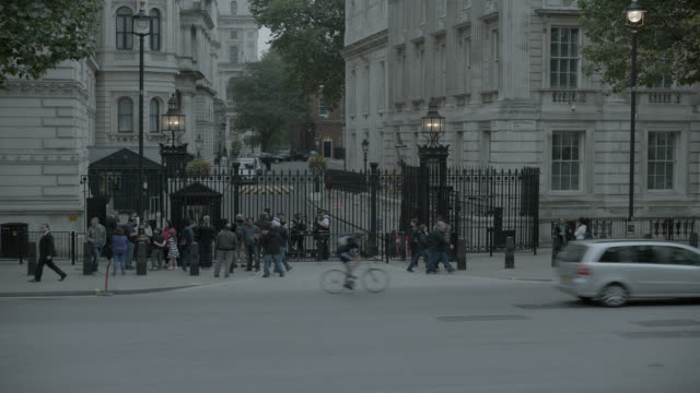 medium angle of entrance to 10 downing street and government buildings. whitehall sw1. pedestrians and tourists visible. cars, taxis, and double deck buses visible on city street. - downing street stock videos & royalty-free footage