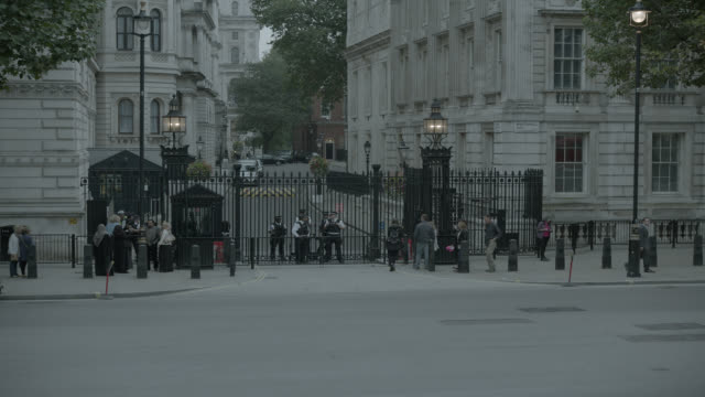 medium angle of entrance to 10 downing street and government buildings. whitehall sw1. pedestrians and tourists visible. cars, taxis, and double deck buses visible on city street. - 10 downing street stock videos & royalty-free footage