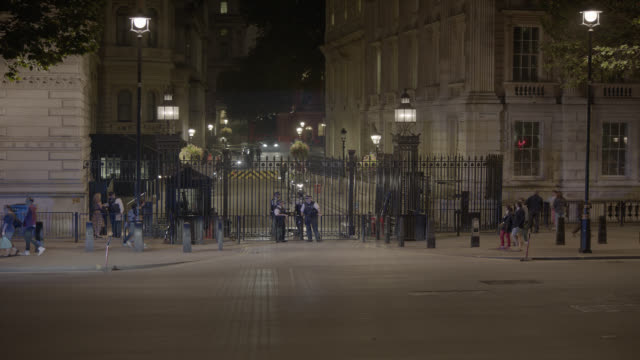 medium angle of entrance to 10 downing street and government buildings. whitehall sw1. pedestrians and tourists visible. cars, taxis, and double deck buses visible on city street. - downing street stock-videos und b-roll-filmmaterial