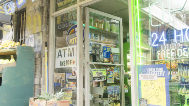 medium angle of entrance to market or convience store. advertisements and fliers on storefront windows. - convenience stock videos and b-roll footage