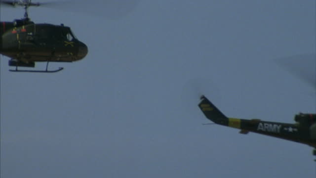 medium angle of five army helicopters flying counter-clockwise in desert. helicopters exit frame to left. - fem objekt bildbanksvideor och videomaterial från bakom kulisserna