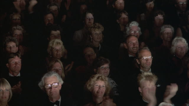 medium angle of formal dressed crowd in evening wear. pans as they begin to applaud, then people slowly stand up for standing ovation. pans left and right to different parts of audience. people begin to sit down at end. - evening wear stock videos & royalty-free footage
