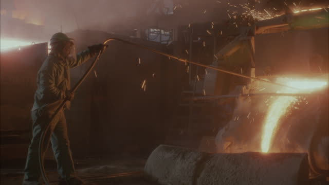 Medium angle of foundry or factory. See worker wearing mask sticking hose or pole into machine with molten steel pouring out. See sparks flying from machine.